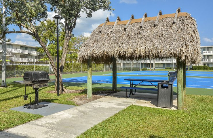 tiki hut with grill and picnic table by the tennis courts