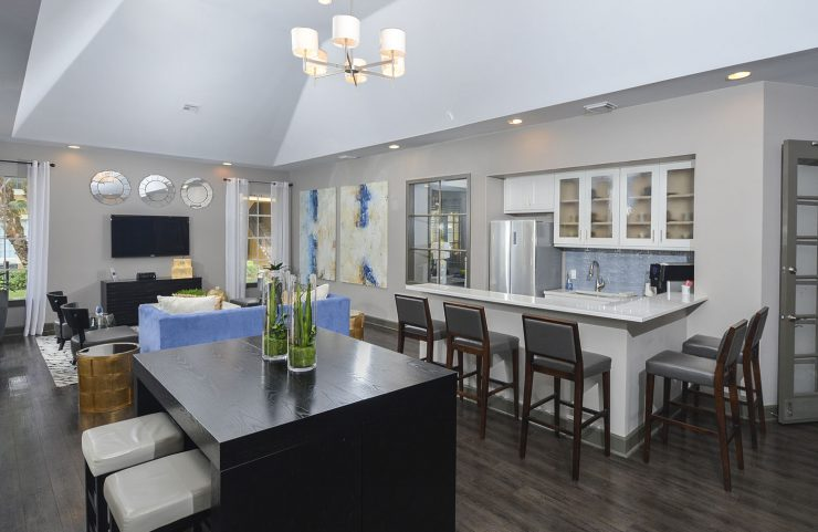 clubhouse with table seating and bar area with a fridge to entertain guests
