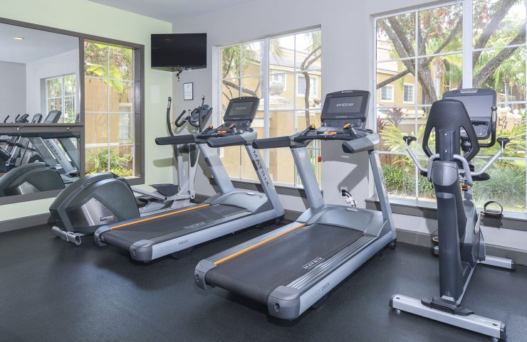 fitness center with one elliptical, two treadmills and a bike facing the window